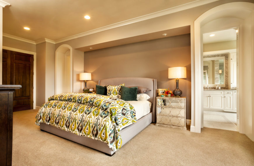 The master bedroom is in light neutrals, but brightens up the space with a green and teal peacock-print bedspread and throw pillows. The nightstand has a mirrored front with a circular pattern.