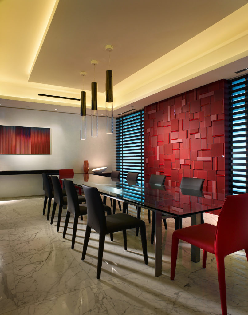 The layered red rectangle look of the archway is repeated on the accent wall behind the formal dining room. The lengthy table is surrounded by chairs with smooth lines, all in black except for the chairs at the head of the table.
