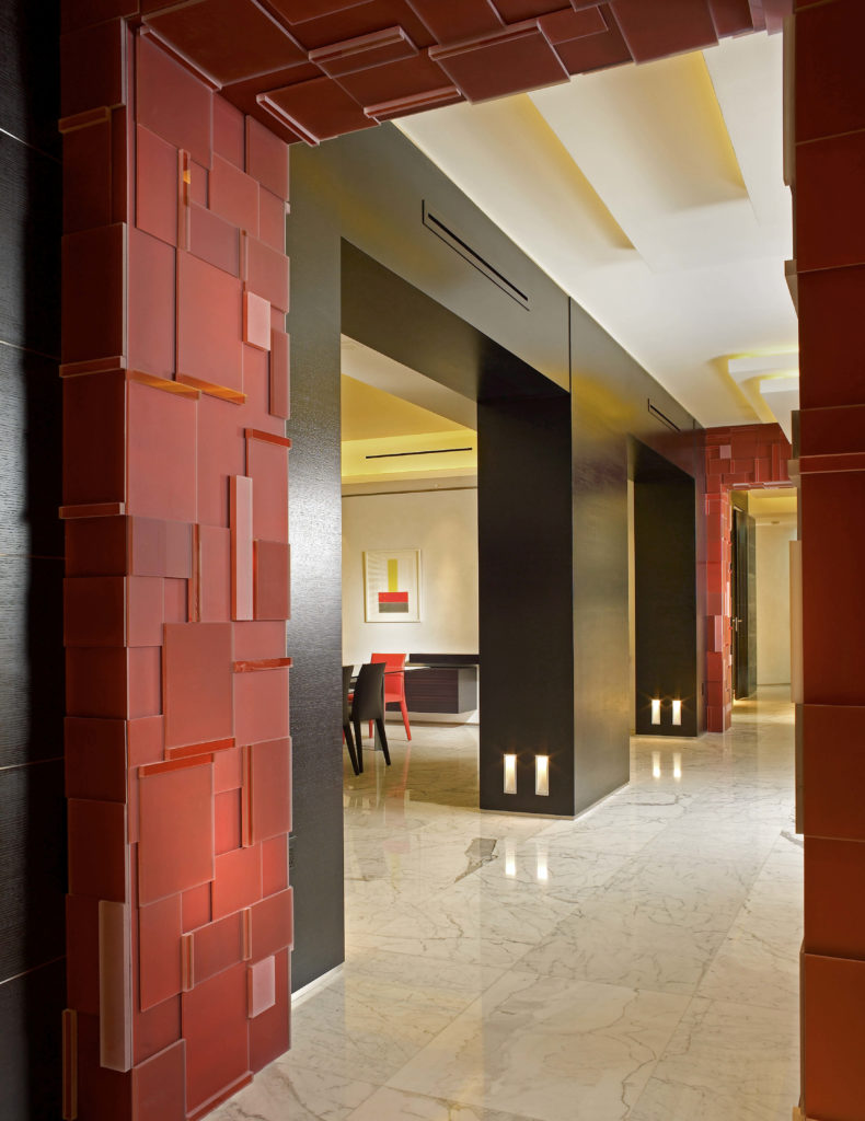 A shot into the dining room from the hallway, with another look at the bold red archway with layers of squares and rectangles on it.