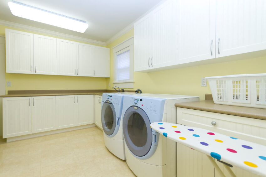 A spacious laundry room with front-loading appliances in pastel yellow walls. The subtle lines of the cabinets are brightened by the colorful polka-dot ironing board.