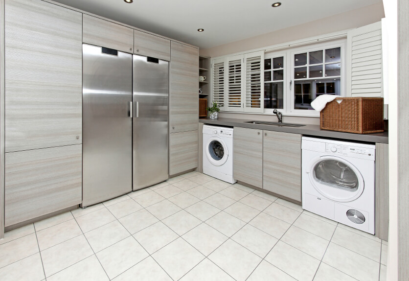 A light gray minimalist laundry room with a front loading washer and dryer. A closet with stainless steel doors acts as a cleaning supply room.