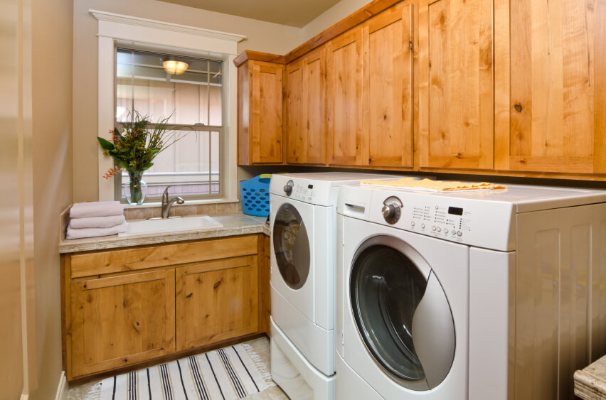 A small laundry room with a sink at the back of the room and front-loading appliances below the natural wood cabinets.