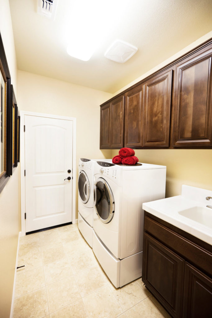 A small laundry room with a set of slim front-loading appliances and a dark wood vanity with a large sink basin.