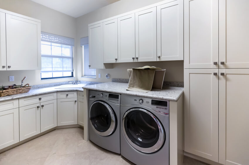 A more spacious laundry room with custom cabinetry around the appliances that provides a solid granite countertop to fold laundry on and set baskets. The sink is situated in the corner by the windows.