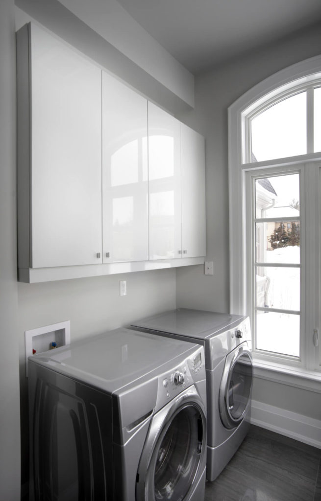 A small laundry room in dove gray and charcoal with glossy light gray front-loading appliances and white baseboard trim.