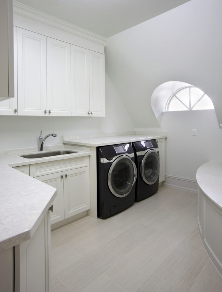 A laundry room with a light color palette and a small bench area to the right. The front-loading appliances are in a sleek black that contrasts beautifully with the rest of the room.