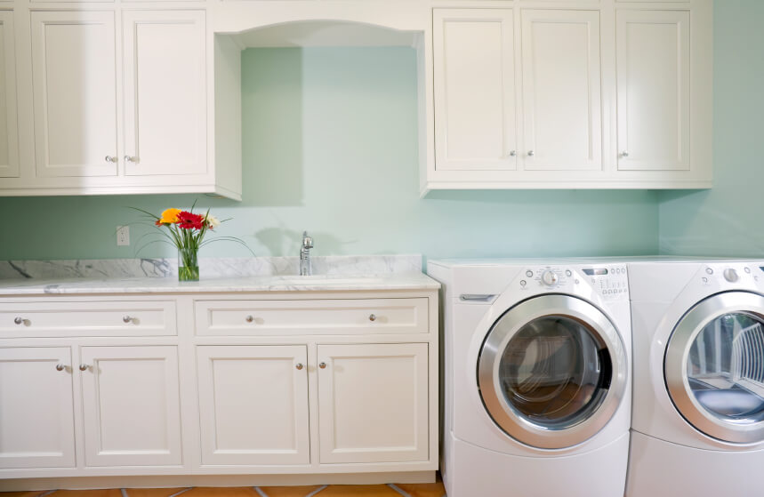 A pretty laundry room in soft mint and pristine white with small chrome fixtures. The countertop is white marble with gray veining.
