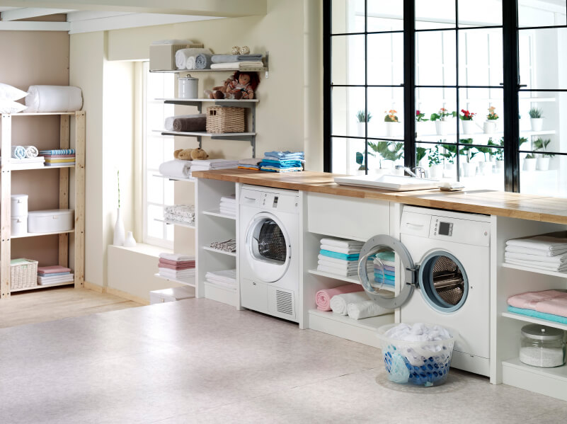 A light and airy laundry room that looks out on the container garden outside. The two-tiered room has a single step down to a light wood linen storage area.
