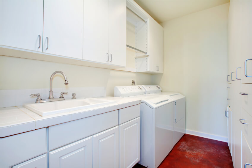 A mostly white laundry room with chrome fixtures and a bold red concrete floor. The room is lined with storage.
