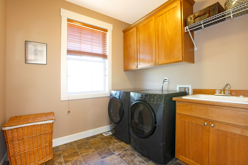A modestly-sized laundry room with light wood cabinetry and black appliances. In the left corner is a wicker laundry hamper.