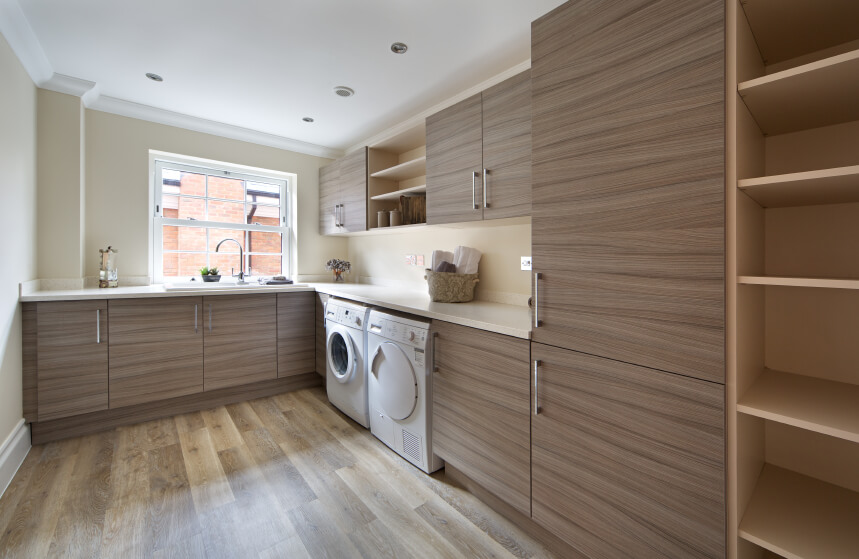 A light, natural wood laundry room with a set of front loading appliances and plenty of both open shelving and cabinets. The multi-tonal hardwood flooring meshes well with the horizontal wood grain of the cabinetry.