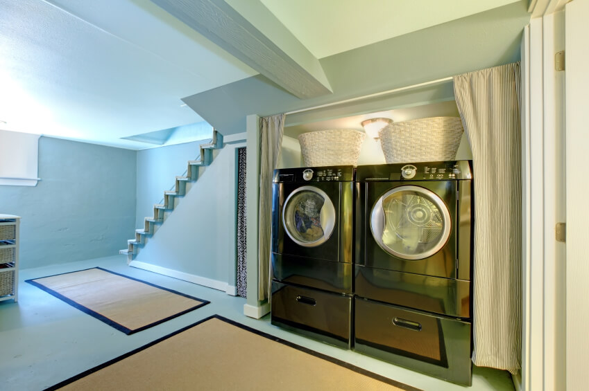 A basement laundry room hidden behind striped curtains. The front-loading washer and dryer are set on top of matching pedestals and have wicker laundry baskets perched on top.