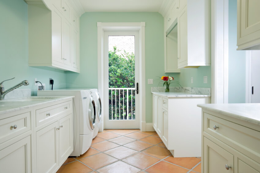 A mint laundry room with plenty of white cabinetry for storage and a door to a back balcony.