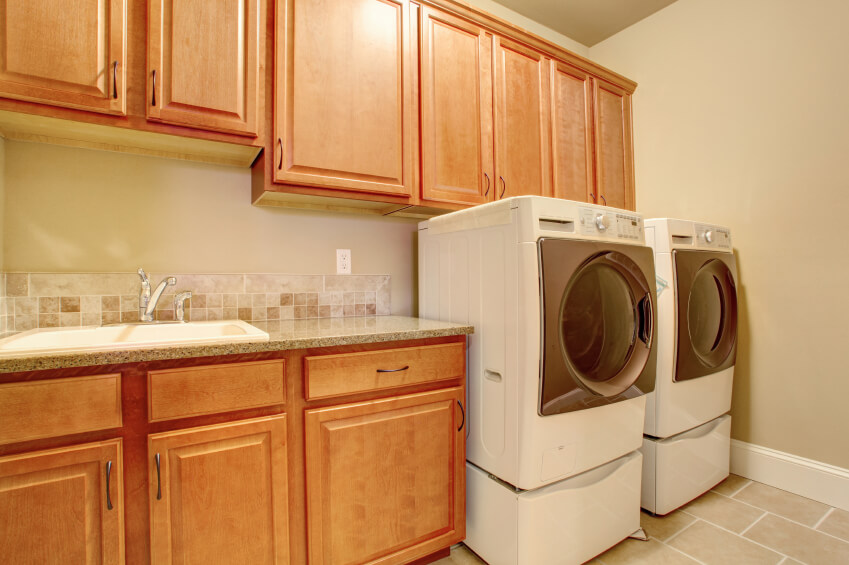 A contemporary laundry room with a neutral color palette and light tile floors.