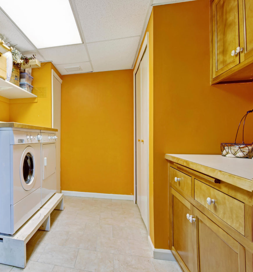 The washer and dryer of this laundry room are on a wooden pedestal with space beneath for storage. The walls are a bright mustard color.