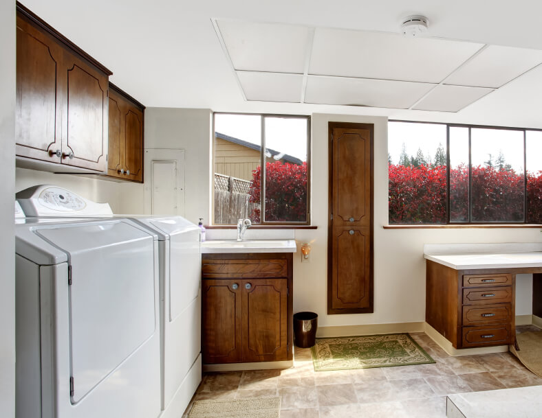 A spacious laundry room with dark wood cabinets and a fold-down ironing board. The front-loading washer and dryer are against the left wall.