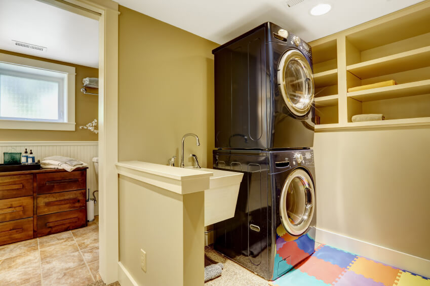 A combination laundry room with a bathroom just around the corner. A deep basin sink is mounted on the wall next to the stacked washer and dryer. In front of the washer and dryer is a interlocking foam mat in bright colors.