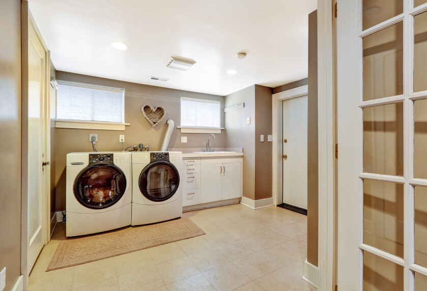 A large laundry room with a small countertop and a back door leading into the garage. The laundry room is separated from the main living area by a glass-paneled door.