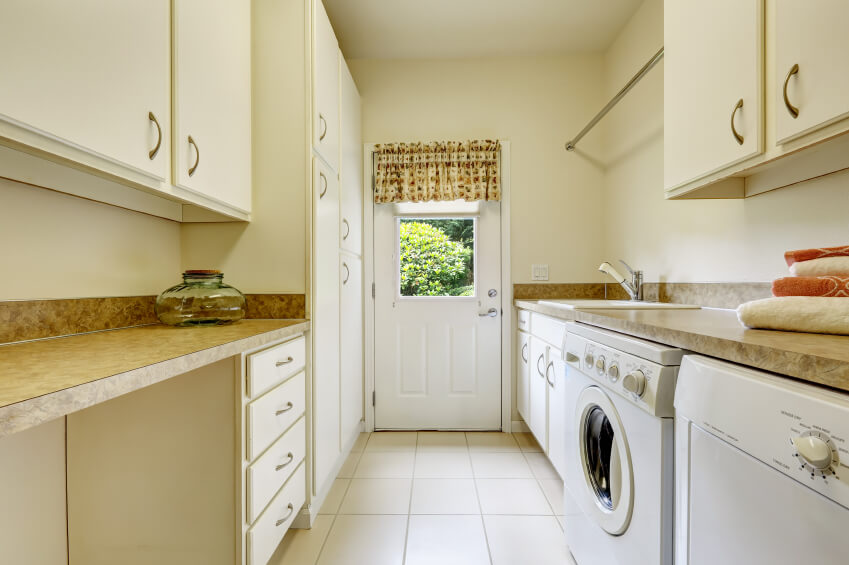 A white and beige country-style laundry room with granite countertops and a door leading to the side garden.