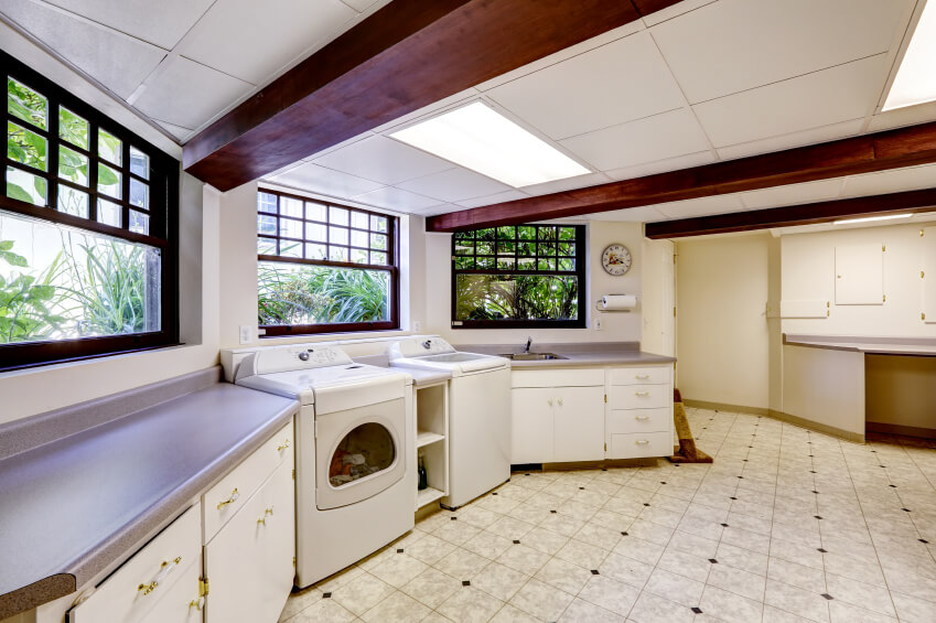 A curved laundry room with exposed wood beams and florescent lighting. This spacious room has plenty of places to fold laundry on the formica countertops.