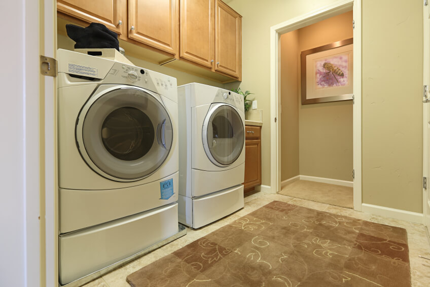 A modestly sized laundry room with an absorbent, thick beige rug with a vine pattern and a set of front-loading appliances on pedestal drawers. Abover the appliances are a set of wall cabinets.