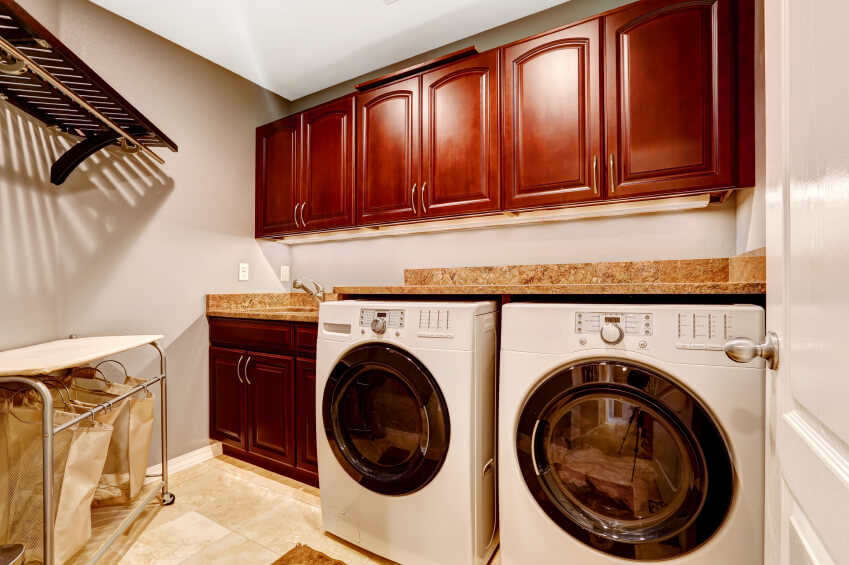A neat and tidy smaller laundry room with stone countertops and rich cabinetry in a red tone.