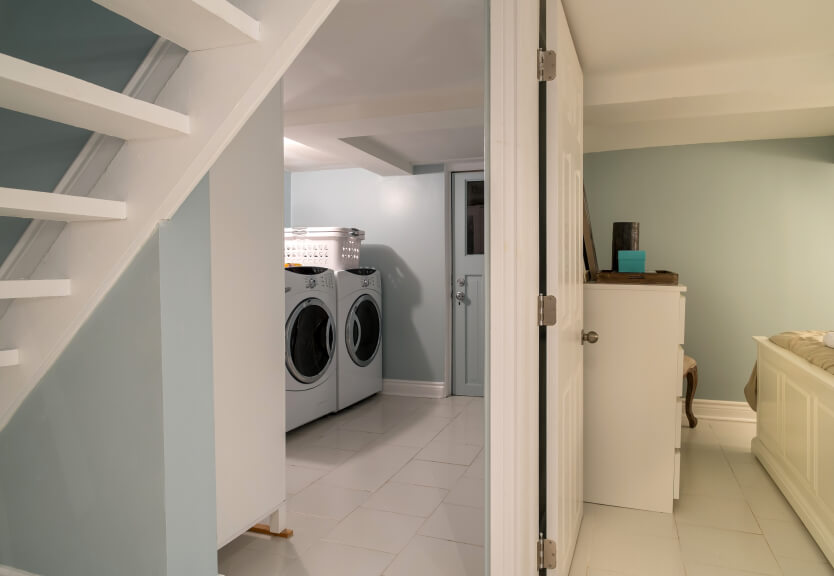 A laundry room near the back door, visible from between the stairs and the living room.