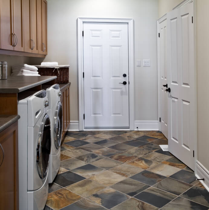 A mudroom and laundry room with a spacious closet and a beautiful tile floor in brown, navy, and beige. The front-loading washer and dryer are tucked beneath the custom cabinetry.