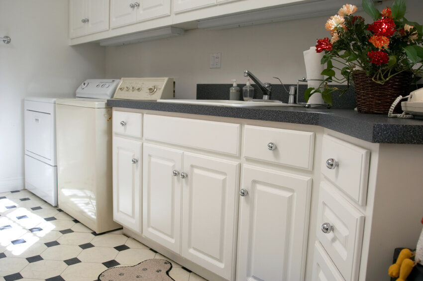 A white laundry room with formica countertops in a dark gray. The laminate floor is in white and black.