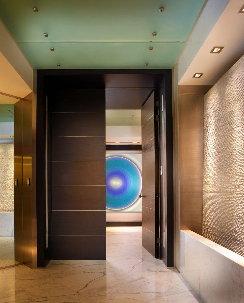 On the other side of the foyer, a striped wooden door leads into a hallway with a large, circular piece of wall art that resembles an eye.
