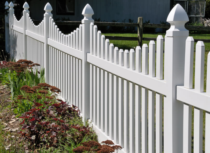 Unlike other fences in this collection, this one has small, sparse landscaping around the edges, with a manicured lawn behind