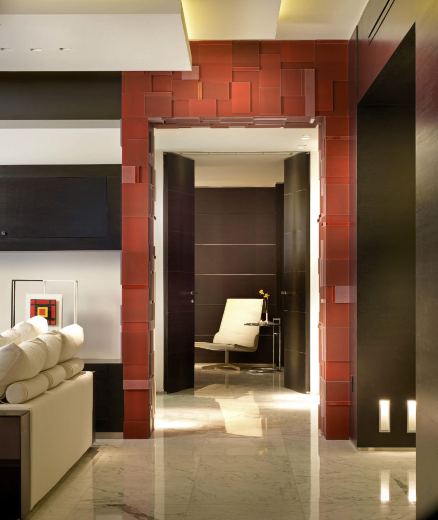The archway of this hallway that leads into another room is a bold red with rectangles and squares of varying sizes in bars around the archway. Double doors in a rich, dark wood open into the room across the hall.