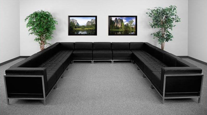 An enormous black sectional with tufted seating and a low profile that would be at home in an upscale waiting room or in your home.