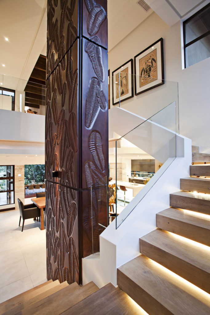 The central staircase wraps around this intricately carved wooden column. The white and light wood tones contrast perfectly, and with the glass railings, aid the wholly contemporary look.