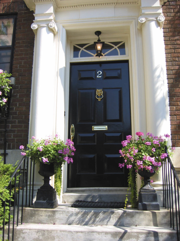 This high gloss door features bright brass mail slot and handle, flanked by a pair of stately white columns.