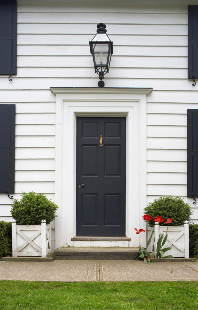 This subtle black door matches the shutter tones creating contrast with this white home. Painted knob blends in seamlessly, while single brass knocker hangs above.