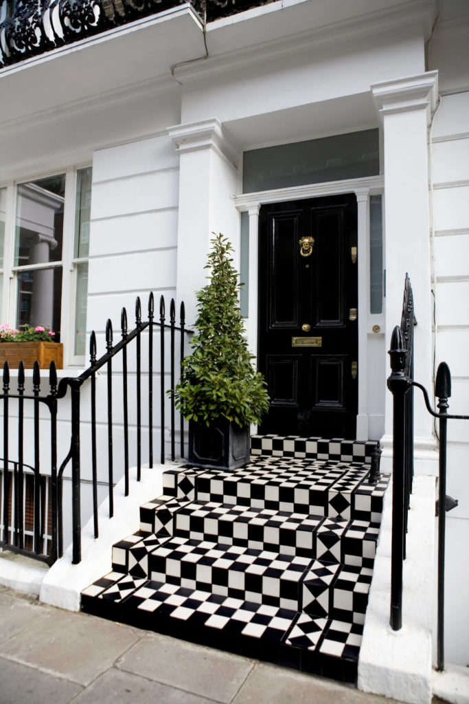 Standing over a vibrant checker patterned set of steps, this black door features a plethora of subtle brass hardware, framed in smoked glass.