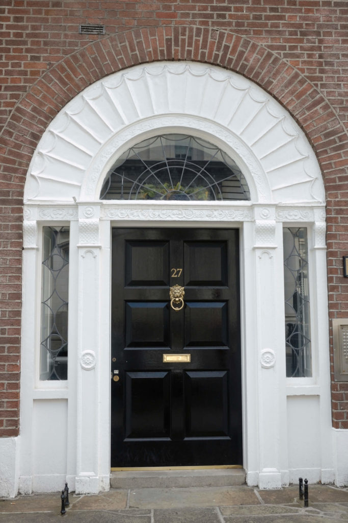 This traditional brick home frames the paneled black door in a white arch, for a high contrast look. We see another bespoke lion head knocker and mail slot in brass here.