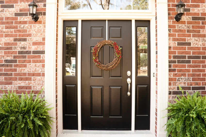This matte black door pops, framed in white on a red brick home.
