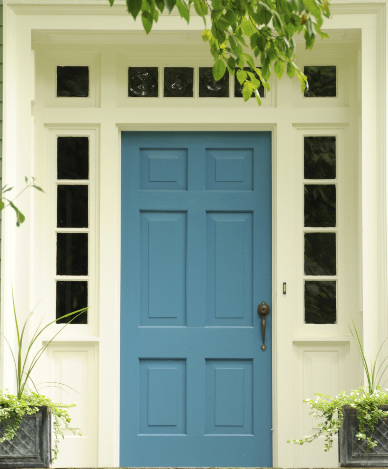 This blue front door has a brass key-entrance door knob and a brass handle. It also has a doorbell installed just beside the handle. The front door has a white painted casing with six glass panels above it. The door also has sidelight windows. Sitting in front of the main entrance are two black planters.