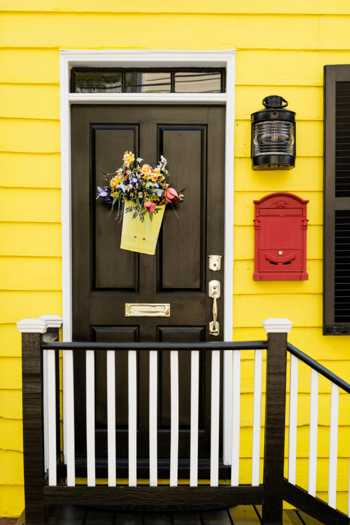 Bright yellow hues frame this simple black door with immaculate brass hardware. Black and white railings lead to the top step.