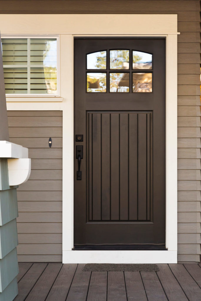 This black door is highlighted by white trim on a neutral grey toned home. Simple array of upper level windows adds interest and function.