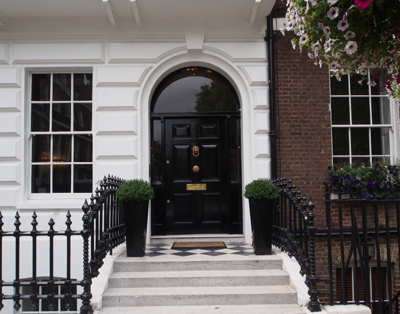 Here we see another porch with checkered tiling beneath a large glossy black door. Wrought iron fencing leads toward a white arched frame with singular transom window above.