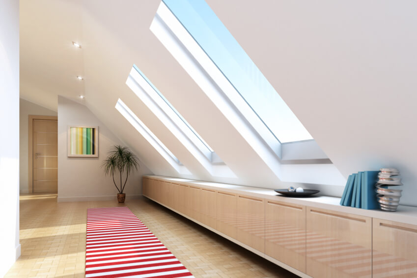 Attic room with cupboard storage and skylights
