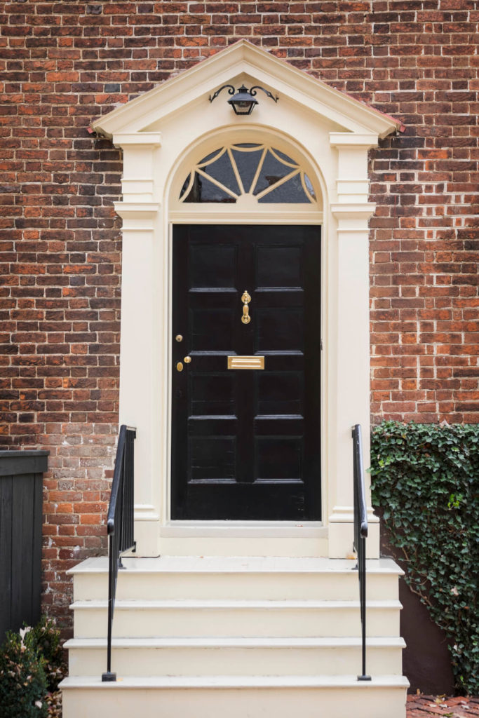 This classic red brick home frames the traditional paneled black door in an off-white tone. Large knocker and mail slot complement the brass hardware.