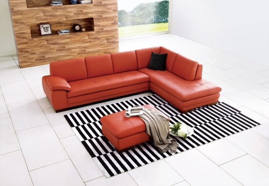 A traditional L-shaped sectional in a bright, bold pumpkin-colored Italian Leather. The padded armrests and light tufting lend this piece an air of sophistication that would be at home in either a modern or contemporary setting.