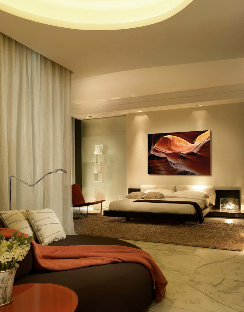 The master bedroom returns to the color palette of browns, reds and taupes. The modern furniture has clean, smooth lines and is paired with modern art. A circular lounge chair acts as a cozy reading and relaxing area.