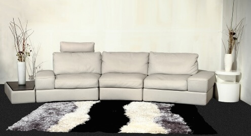 This leather sectional is a versatile option in a very modern style. As an extra level of comfort, each of the three seats has a headrest that can be positioned up or down to suit the individual's needs. The trapezoidal end table can be used as a coffee table or an end table as shown below.