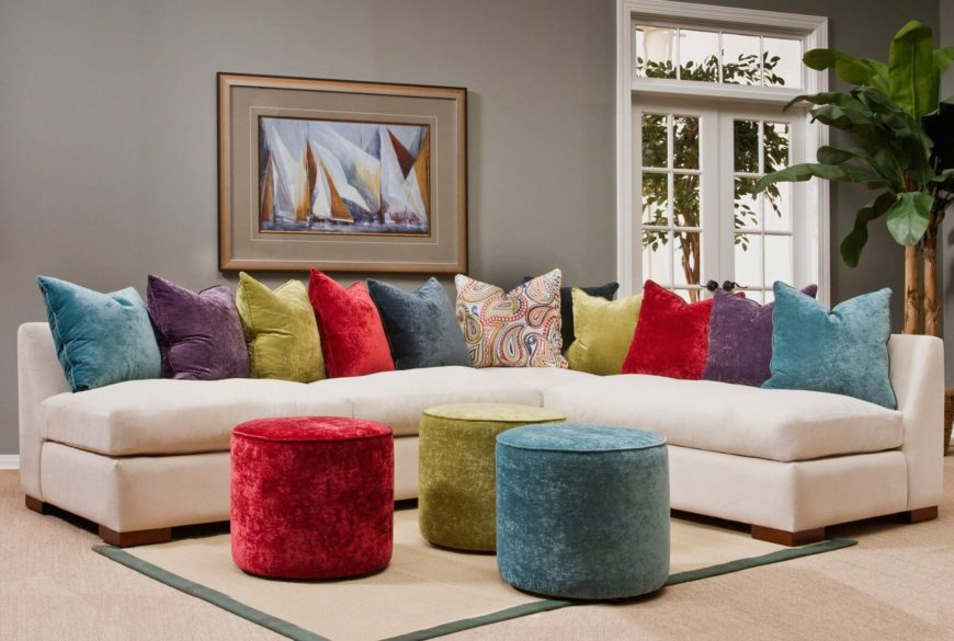 A cream crushed velvet sectional with a loose cushion back of rainbow pillows and a paisley patterned pillow. The armless design and neutral upholstery allow this sofa to belong to any size space with ease.