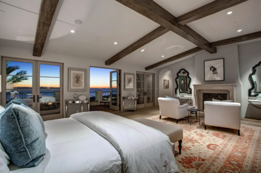 The enormous room has been transformed into the master bedroom, with the room's hardwood floors covered by a traditionally styled area rug. Two wide armchairs are positioned in front of the fireplace, which is flanked on either side by ornate mirrors.